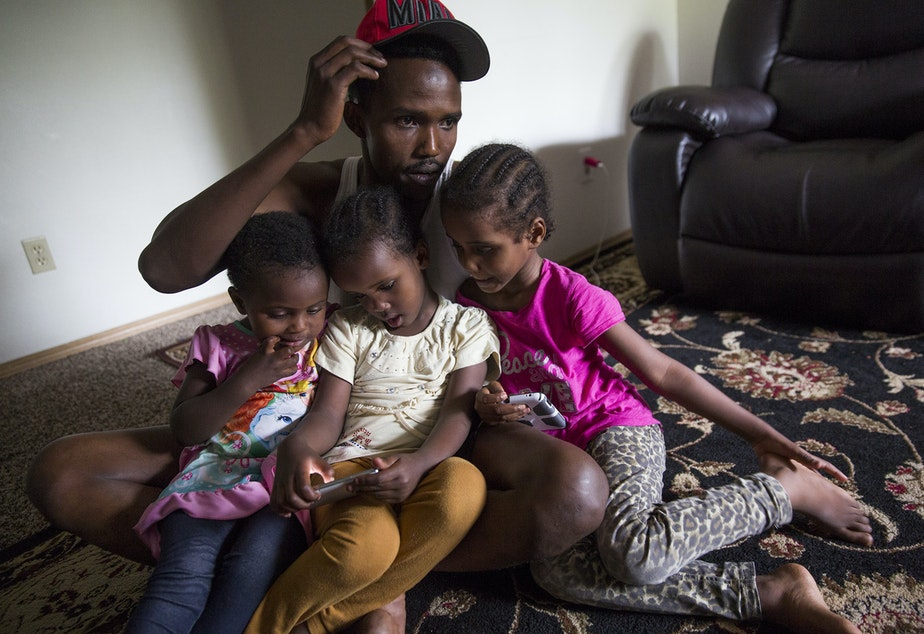 caption: Osman Mohamed, of Somalia, and his three daughters, ages 2, 4 and 5. Osmon hoped to find paradise in Seattle, but in his first year, his family witnessed a shooting and he was hit by a car.