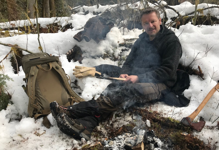 caption: Chris Morgan building a fire while out recording 'The Wild' on location.