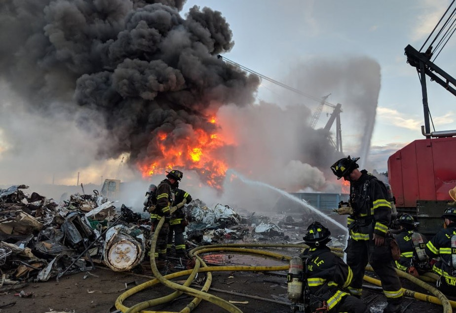 Seattle firefighters tackle a blaze amid scrapped cars along the Duwamish River on June 26.