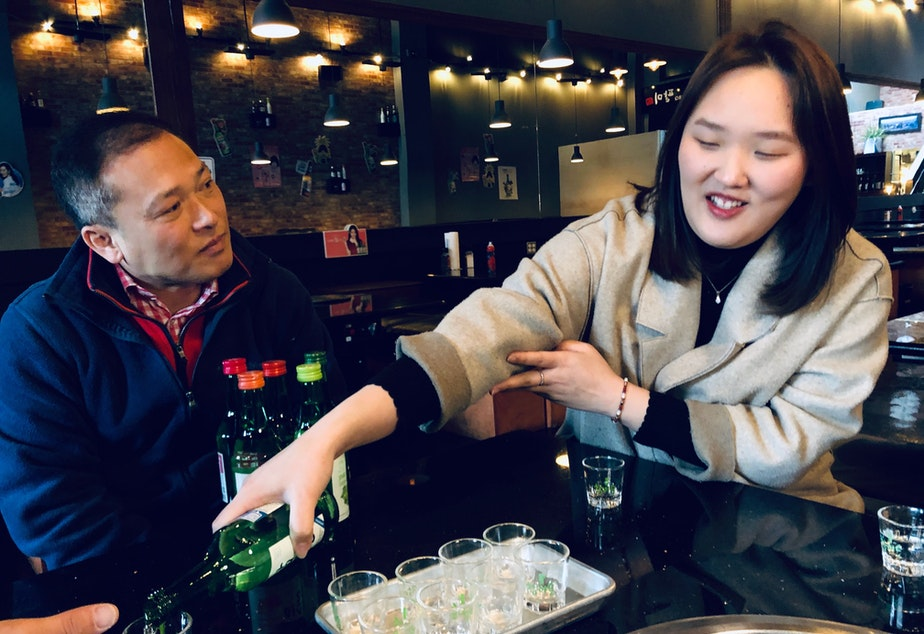 caption: The proper way to serve soju comes from traditional Korean culture.