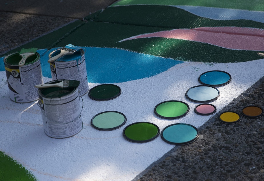 caption: The tops of paint cans are shown as the Black Lives Matter street mural is repainted by local artists on Friday, October 2, 2020, on E. Pine Street in Seattle.