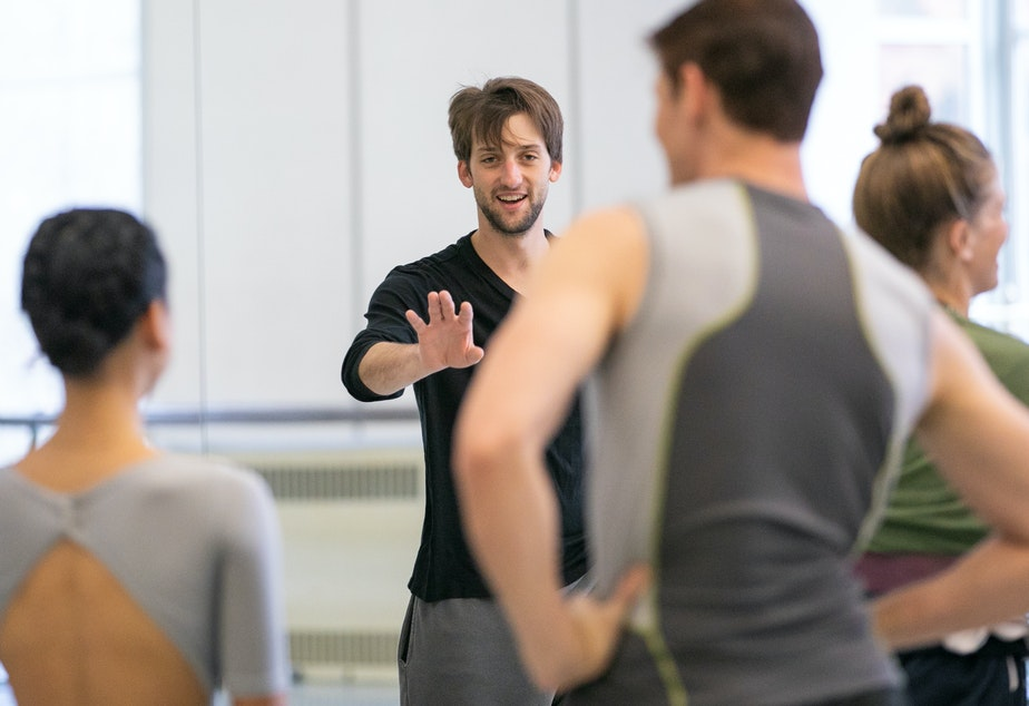 "caption: Pacific Northwest Ballet dancer Miles Pertl rehearses his fellow company members for this week's debut of his ballet ""Wash of Gray."""
