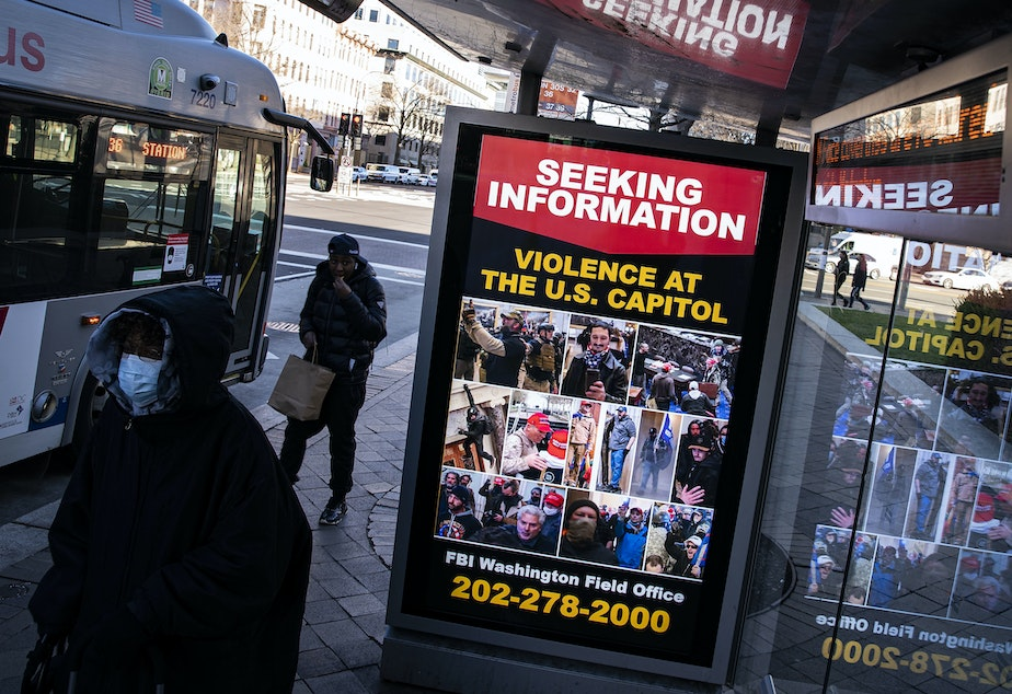 caption: At a bus stop on Pennsylvania Avenue Northwest in Washington, D.C., a notice from the FBI seeks information about people pictured during the riot at the U.S. Capitol on Wednesday.