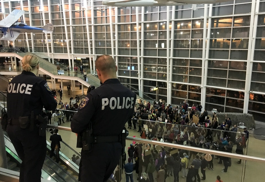 caption: Police look out over a growing protest at Sea-Tac International Airport, where up to 13 people have been detained one day after President Donald Trump issued an executive order banning people from seven Muslim countries.