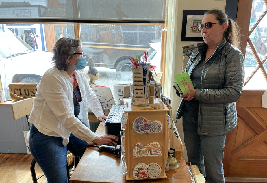 caption: Meg Olson speaks to a visitor at the Kingfisher Bookstore