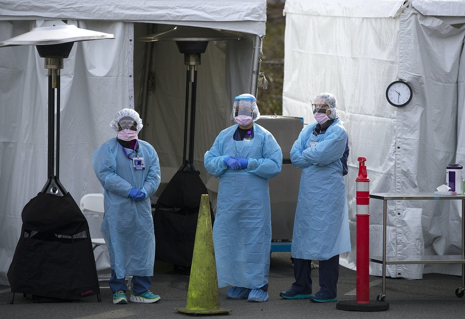 caption: UW Medicine nurses wait for patients to arrive to be tested for coronavirus on Tuesday, March 17, 2020, at the University of Washington Northwest Outpatient Medical Center drive-through testing area on Meridian Avenue North in Seattle.