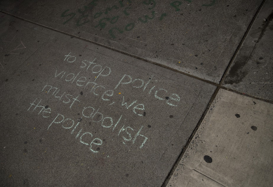 caption: 'To stop police violence, we must abolish the police,' reads chalk writing on a sidewalk at the intersection of 11th Avenue and East Pine Street on Tuesday, April 20, 2021, following the reading of the guilty verdict in the trial of Derek Chauvin for the murder of George Floyd, in Seattle.