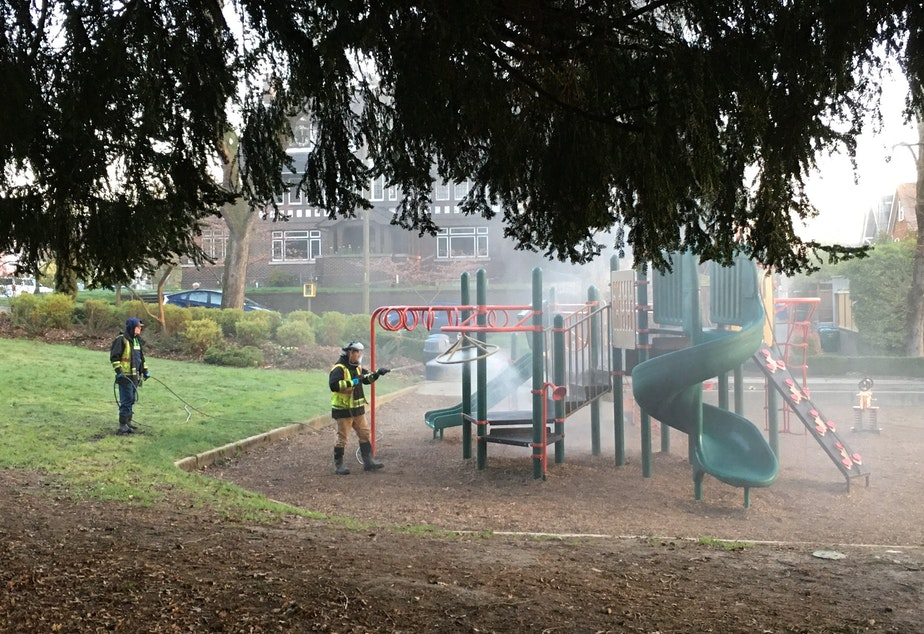 "caption: Seattle Parks and Rec staff spray down playground equipment at Roanoke Park with ""H2Orange2""which is a mix of hydrogen peroxide and orange extract."