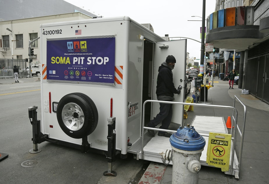 caption: An attendant exits a 'Pit Stop' public toilet on Sixth Street, Thursday, Aug. 1, 2019, in San Francisco. A 5-year-old portable toilet program in San Francisco that provides homeless people with a private place to go has expanded to 25 locations in the city and has spread to Los Angeles.