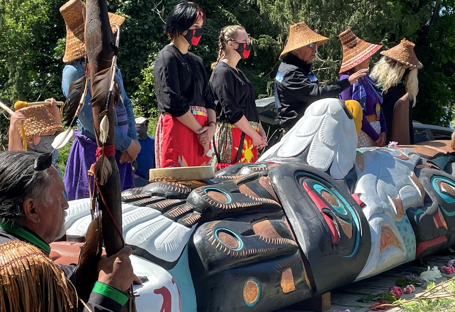 caption: Lead carver Jewell Praying Wolf James (left), known as Sit ki kadem, looks on while his brother Douglas James (center), known as Sit ki kadem, speaks to a large crowd on Orcas Island