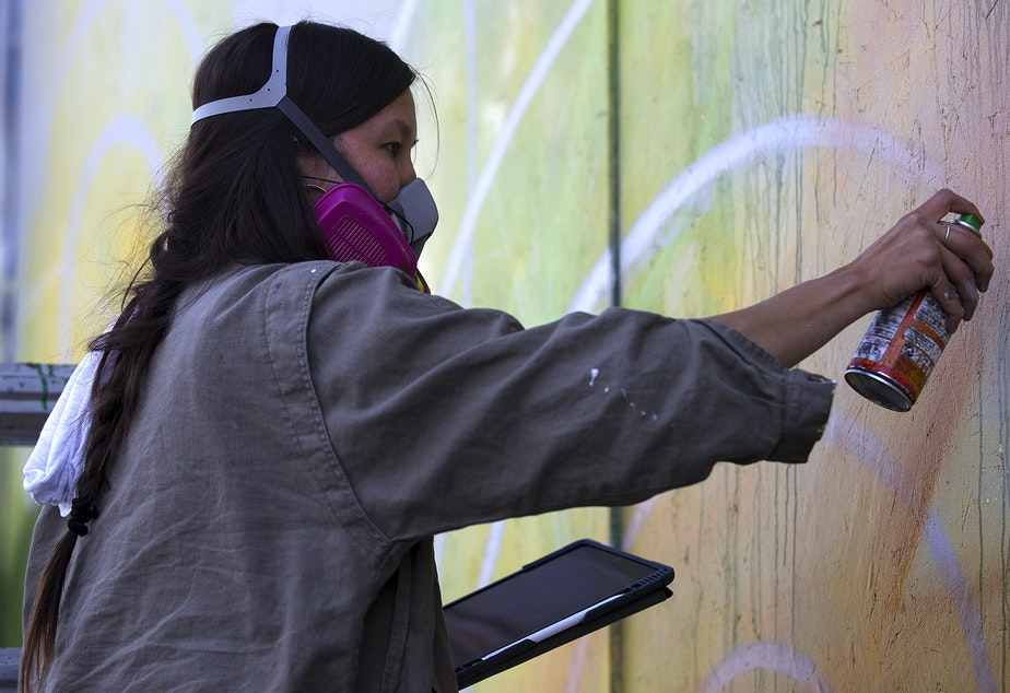"caption: Artist Mari Shibuya works on a mural on Monday, April 20, 2020, at the intersection of East Pine Street and 10th Avenue in Seattle. The mural reads, ""New systems will grow if we tend to them together."""