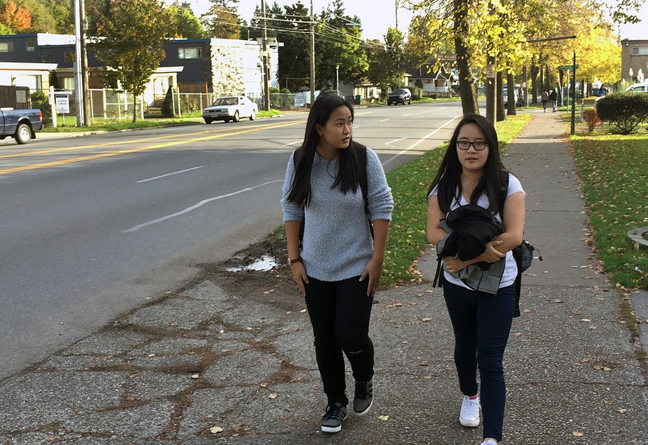 Emily Au, right, a junior at Rainier Beach High School, walks home from school with her cousin, Rebecca Chung. Au says the walk is dangerous, and that some students skip class or show up tardy because they don't want to walk in the dark.