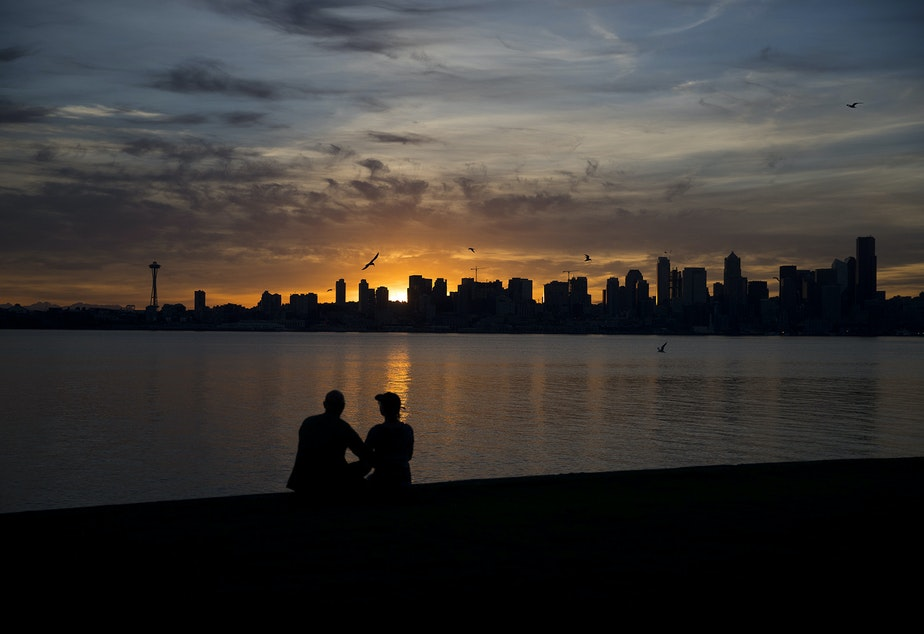 caption: David and Meg Haggerty watch the sun come up on Wednesday, June 12, 2019 at 5:14 a.m. from Alki Ave Southwest in Seattle.
