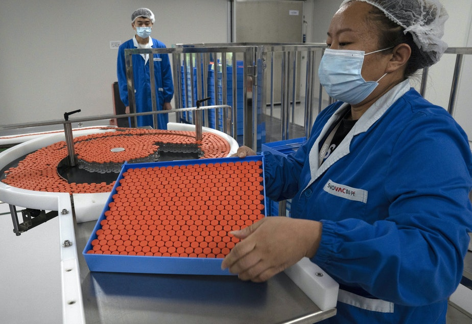 caption: A worker feeds vials for production of a vaccine for COVID-19 at the SinoVac vaccine factory in Beijing. China said on Friday that it is joining the COVID-19 vaccine alliance known as COVAX.