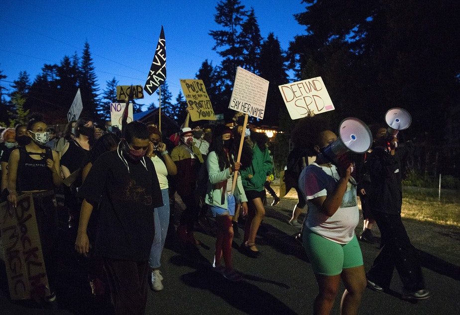 """caption: The Everyday March group heads toward Seattle City Councilmember Debora Juarez's home in an effort to have a dialogue about racial justice and police brutality on Tuesday, August 4, 2020, in the Victory Heights neighborhood of Seattle. """"It is on us,"""" said organizer Tealshawn Turner. """"It is our duty, our obligation, our responsibility to come out here and stand up for the next generation. You have to speak life into these children."""""""