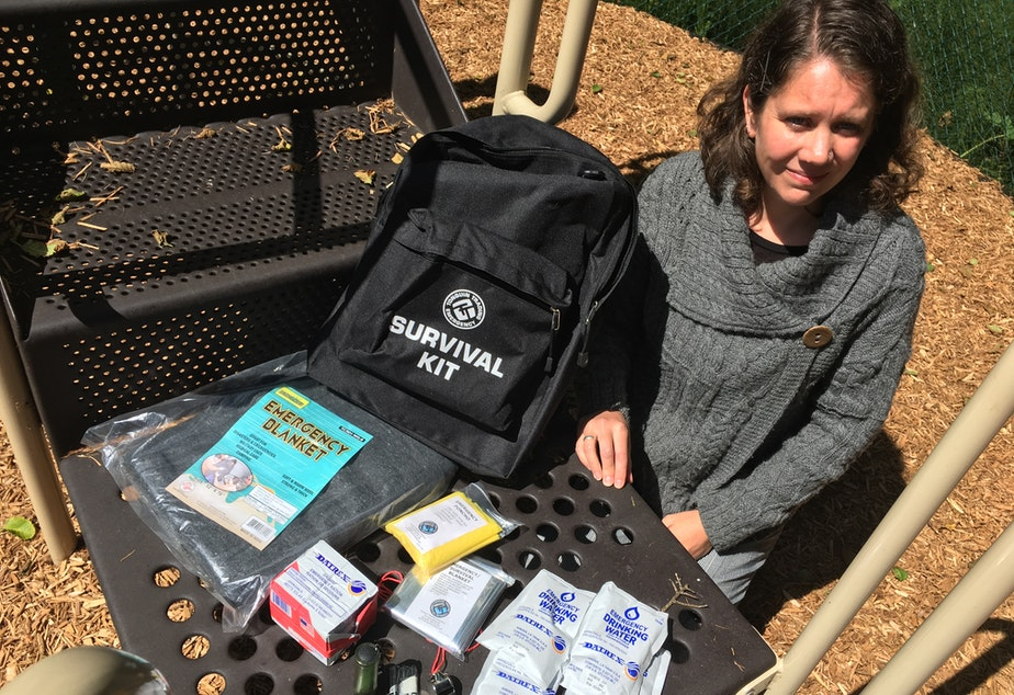 caption: Cannon Beach Academy director Amy Fredrickson with one of the school's 55 survival kits.