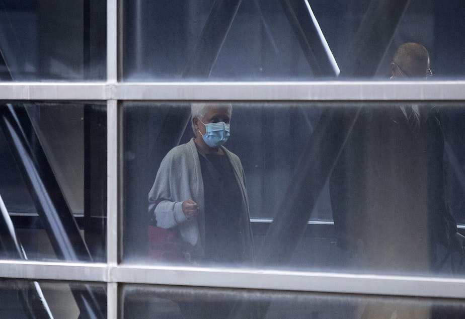 caption: Masked travelers walk through a skybridge on Monday, May 18, 2020, at Seattle-Tacoma International Airport in Seattle. All passengers and employees traveling through the airport are required to wear face coverings beginning today, Monday, May 18.