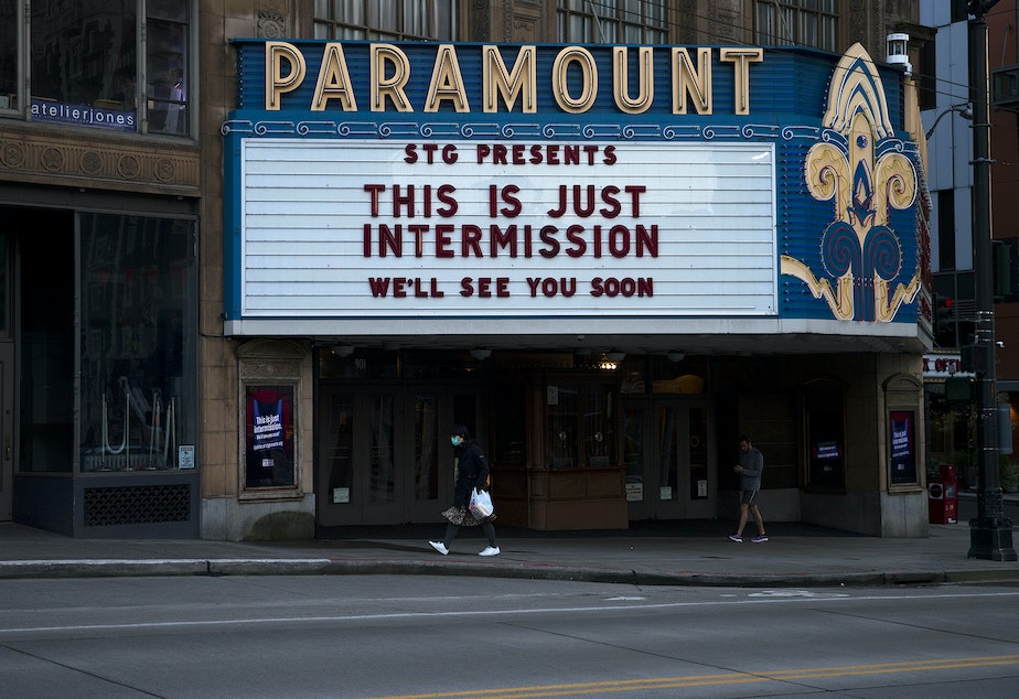 "caption: A pedestrian walks underneath the Paramount Theater marquee at the end of March along Pine Street in Seattle. ""This is just intermission,  we'll see you soon,"" reads the sign."