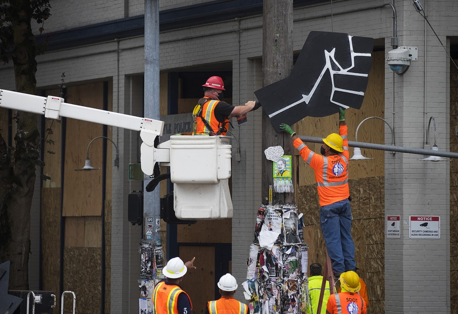caption: Seattle Department of Transportation employees remove a Black power fist from a telephone pole outside of the East Precinct building after the Capitol Hill Organized Protest zone, CHOP, was cleared early Wednesday morning, July 1, 2020, in Seattle.