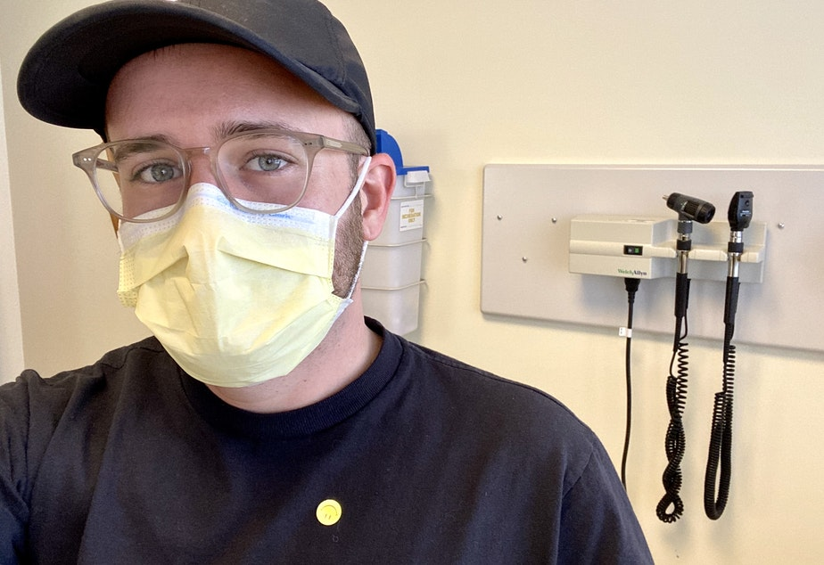 caption: Ian Haydon awaits his first coronavirus vaccine injection