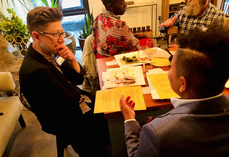 KUOW Curiosity Club members Keri Zierler (left) and Mellina White Cusack talk during Queeriosity Club at The Cloud Room in Seattle. KUOW producer Adwoa Gyimah-Brempong talks with Club member Jeffrey Howard in the background. June 7, 2019.