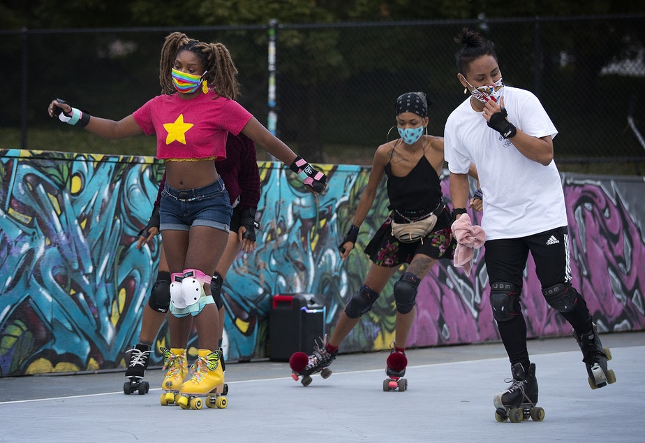 caption: Zenobia Taylor, left, skates on Tuesday, September 22, 2020, at the Judkins Park sports courts in Seattle.