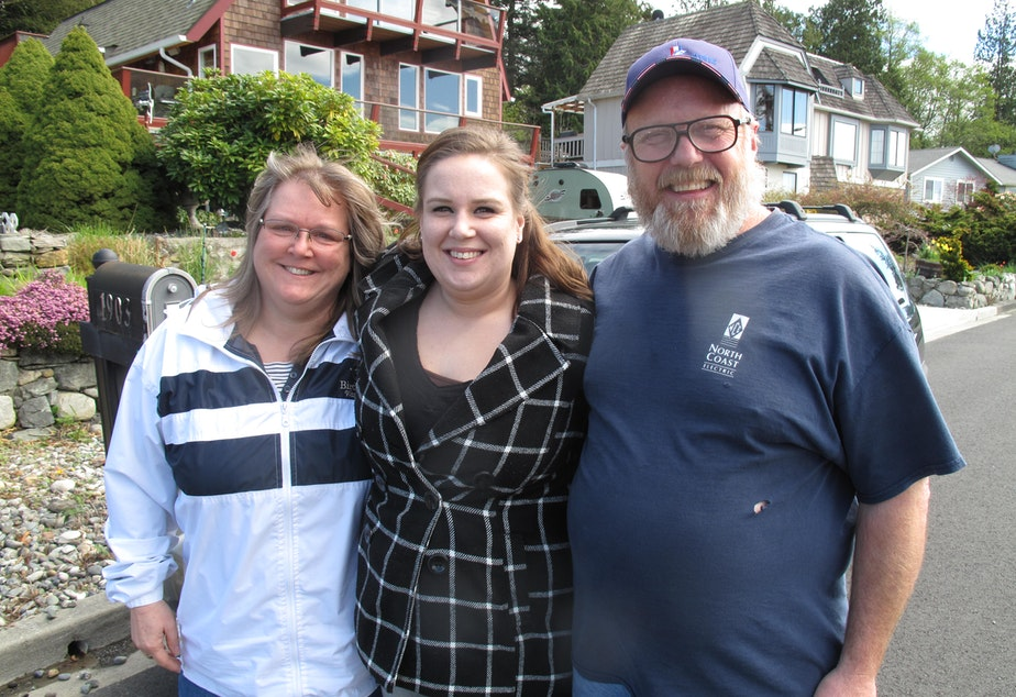 caption: Justina Bauthues (center) poses for a photo with her parents, Lisa and Tom Hilton.