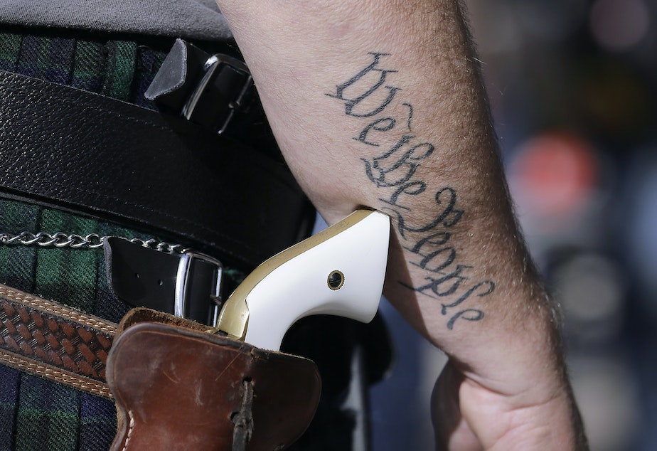 caption: FILE - In this Jan. 26, 2015, file photo, Scott Smith, a supporter of open carry gun laws, wears a pistol as he prepares for a rally in support of open carry gun laws at the Capitol, in Austin, Texas.
