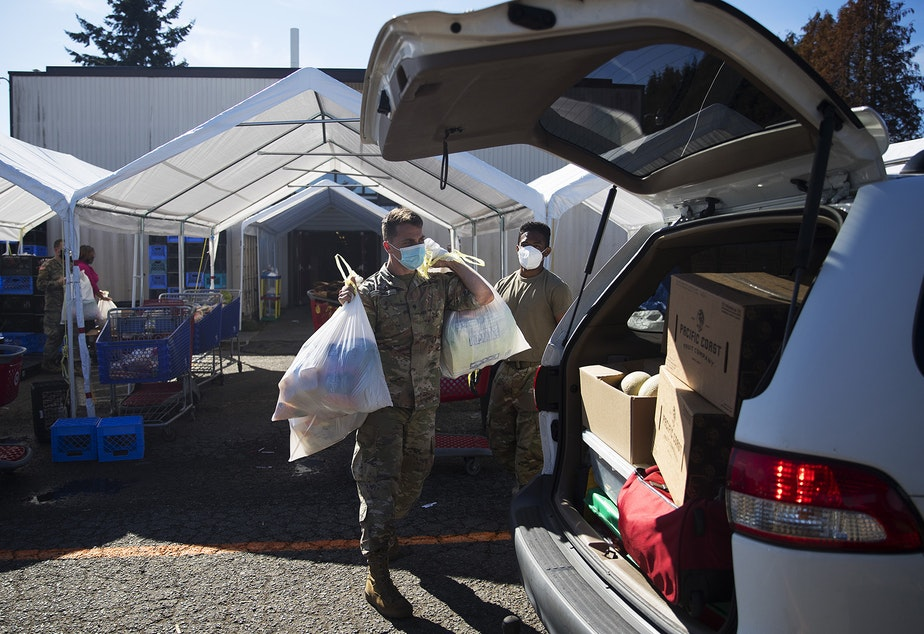 caption: Spc. Erik Jones, left, and Spc. Andre Bhatt with the Washington National Guard load bags and boxes of food into the back of a vehicle on Tuesday, September 22, 2020, at the Tukwila Pantry Food Bank on South 140th Street in Tukwila.