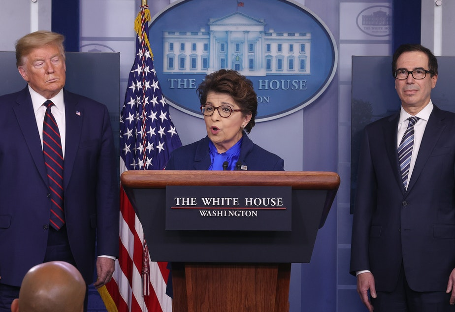 caption: Small Business Administration chief Jovita Carranza speaks at the White House as President Trump and Treasury Secretary Steven Mnuchin look on. Some small business owners are facing delays in applying for a new loan program.