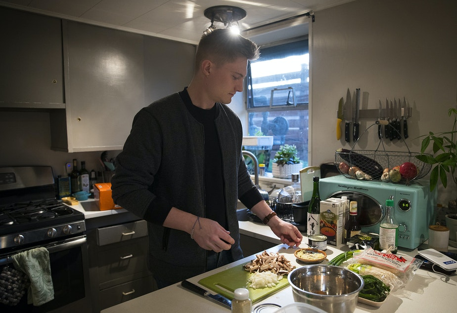 caption: Biggest Carbon Loser Will Wilson cooks a low-carbon meal at his apartment in February in Seattle.