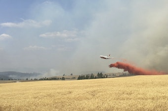 In this photo released by The Eastern Area Incident Management Team, a Very Large Air Tanker (VLAT) drops retardant on a wheat field as crews continue to battle a wildfire in eastern Washington state Sunday, Aug. 5, 2018.