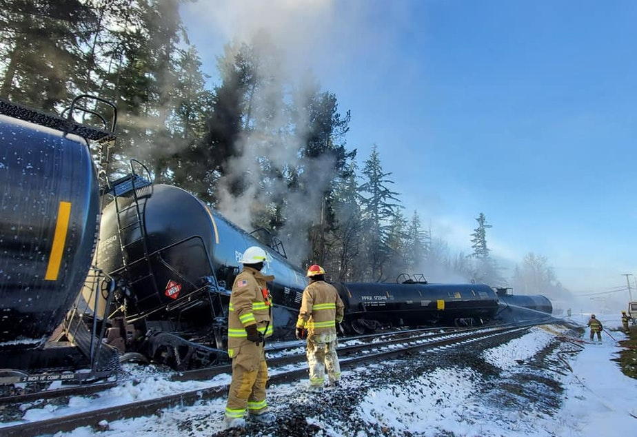 caption: Firefighters work on an oil train that derailed in Custer, Washington, on Dec. 22.