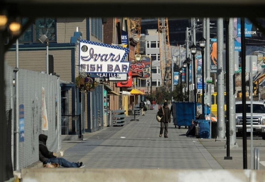 caption: The sidewalk along Alaskan Way in front of Seattle's iconic Ivar's Fish Bar restaurant is nearly empty, Friday, April 10, 2020, as seen from a construction walkway near the Colman Ferry Terminal in Seattle.