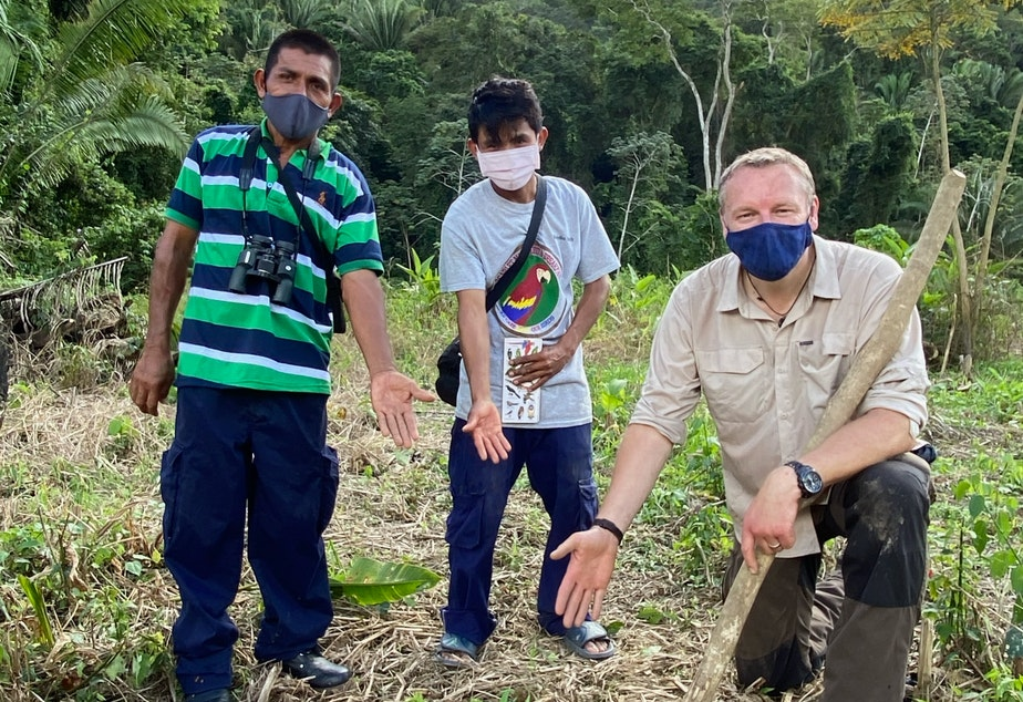 caption: Chris Morgan (right) shows off a newly planted tree that will provide food for scarlet macaws along with Florentino Sub (left) and his son Rojilio (center)