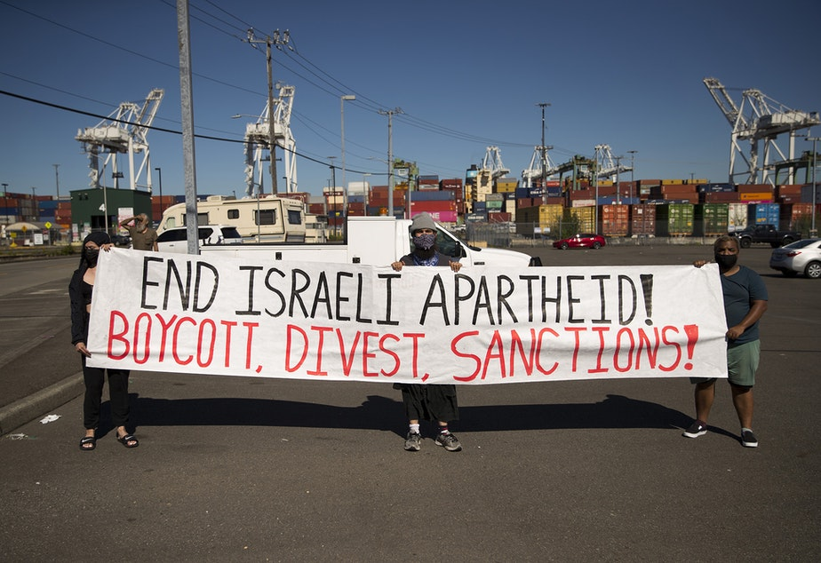 caption: Activists and allies of the Palestinian feminist organization Falastiniyat hold a sign calling for the end to Israeli apartheid while others block an intersection in protest of the Israeli Zim San Diego Vessel, on Thursday, June 17, 2021, at the Port of Seattle.