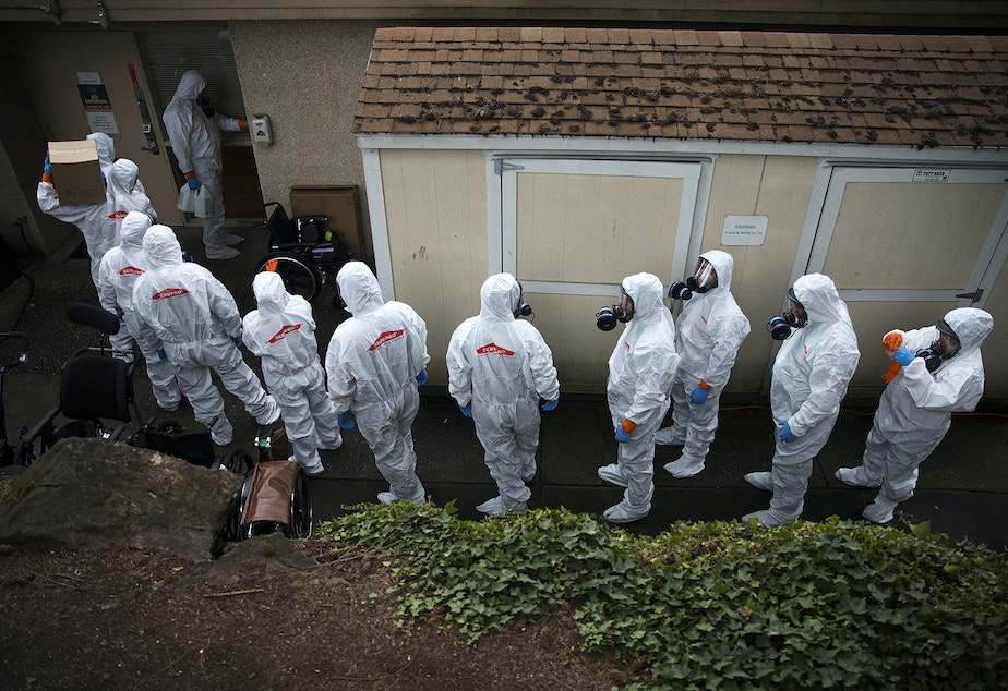 caption: Members of a Servpro cleaning crew line up before entering the Life Care Center of Kirkland, the long-term care facility at the epicenter of the first coronavirus outbreak in the U.S., on Wednesday, March 11, 2020, in Kirkland. As of Wednesday, March 11, Washington state had reported 29 total Covid-19 related deaths.