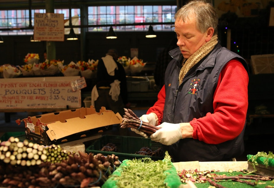caption: Mike Osborn at Sosio's Fruit and Produce in the Pike Place Market on March 25, 2020. Behind him and across the aisle are flower bouquets he's selling for flower vendors that can't legally open.