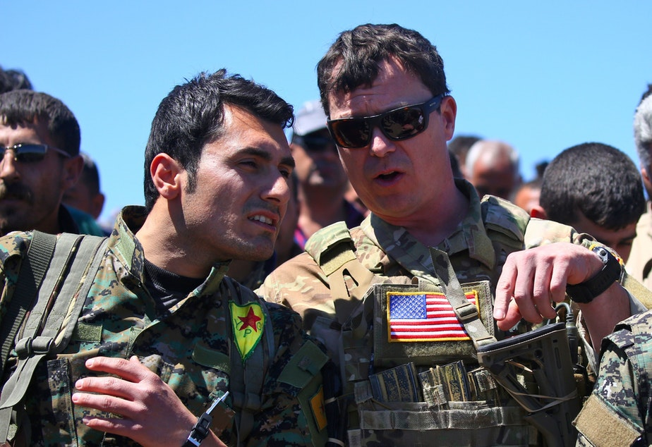 caption: President Trump's plan for the Turkish-Syrian border contradicts recommendations from top officials in the Pentagon and the State Department. In this 2017 photo, a U.S. officer from the coalition against ISIS speaks with a fighter from the Kurdish People's Protection Units (YPG) at the site of Turkish airstrikes near the northeastern Syrian Kurdish town of Derik.