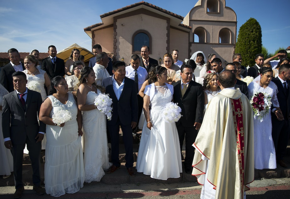 Alejandro Trejo, or Father Alex, arranges couples before a group portrait is taken by a wedding photographer in front of the church on Sunday, June 2, 2019, at Our Lady of the Desert Church in Mattawa.