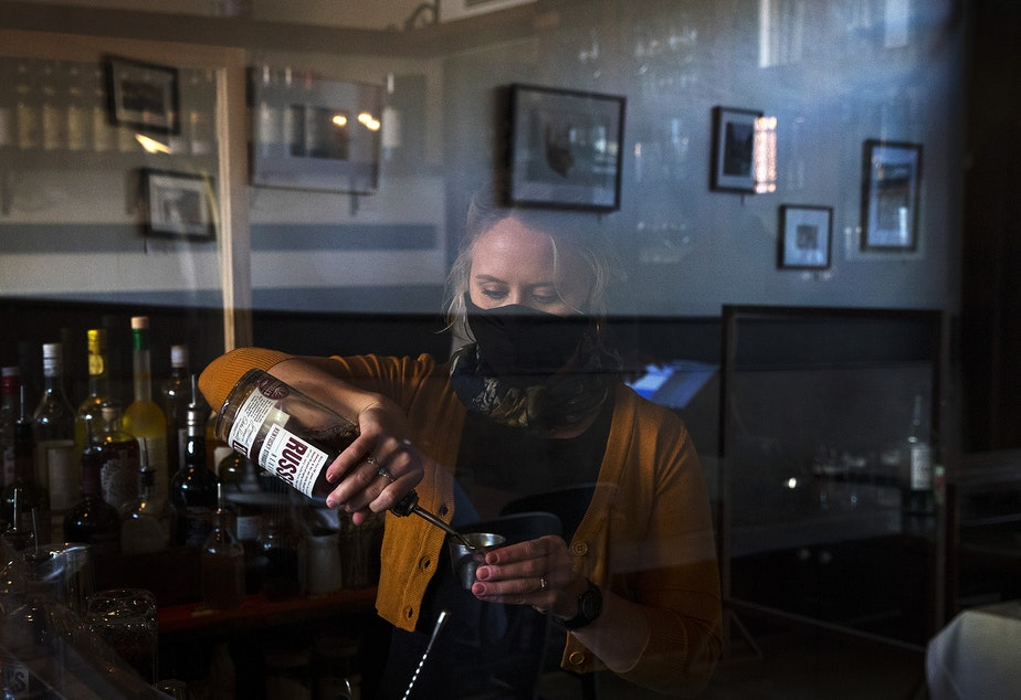 caption: Bartender Cooper Smith makes a drink for a customer behind a sheet of plexiglass on Wednesday, October 21, 2020, at Spinasse on Capitol Hill in Seattle.