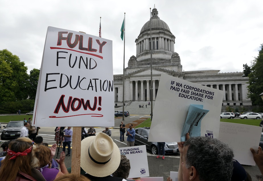 caption: Demonstrators on the steps of the Temple of Justice advocate for more state spending on education, Sept. 3, 2014, in Olympia. The court ordered lawmakers to explain why they haven't followed its orders to fix the way Washington pays for public education.