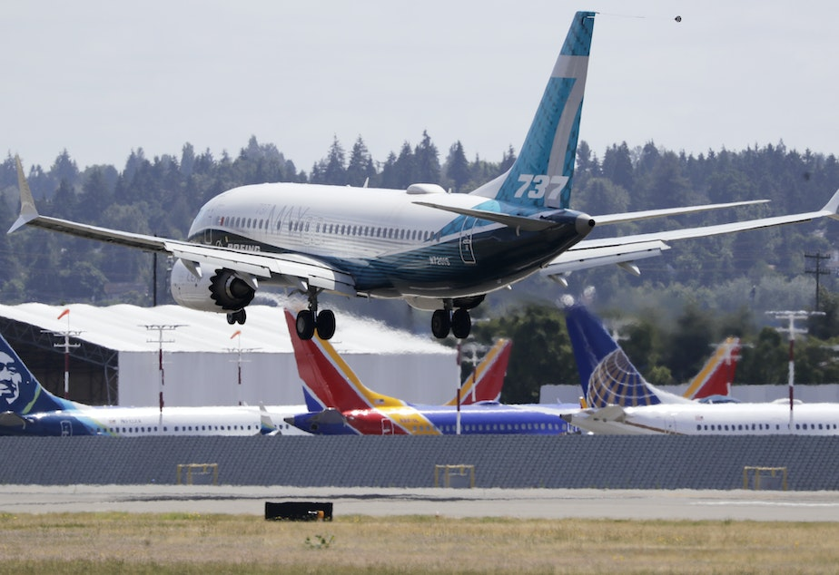 caption: A Boeing 737 Max heads to a landing past grounded Max jets at Seattle's Boeing Field, following a test flight in June. It was the first of three days of re-certification test flights that mark a step toward returning the aircraft to passenger service.