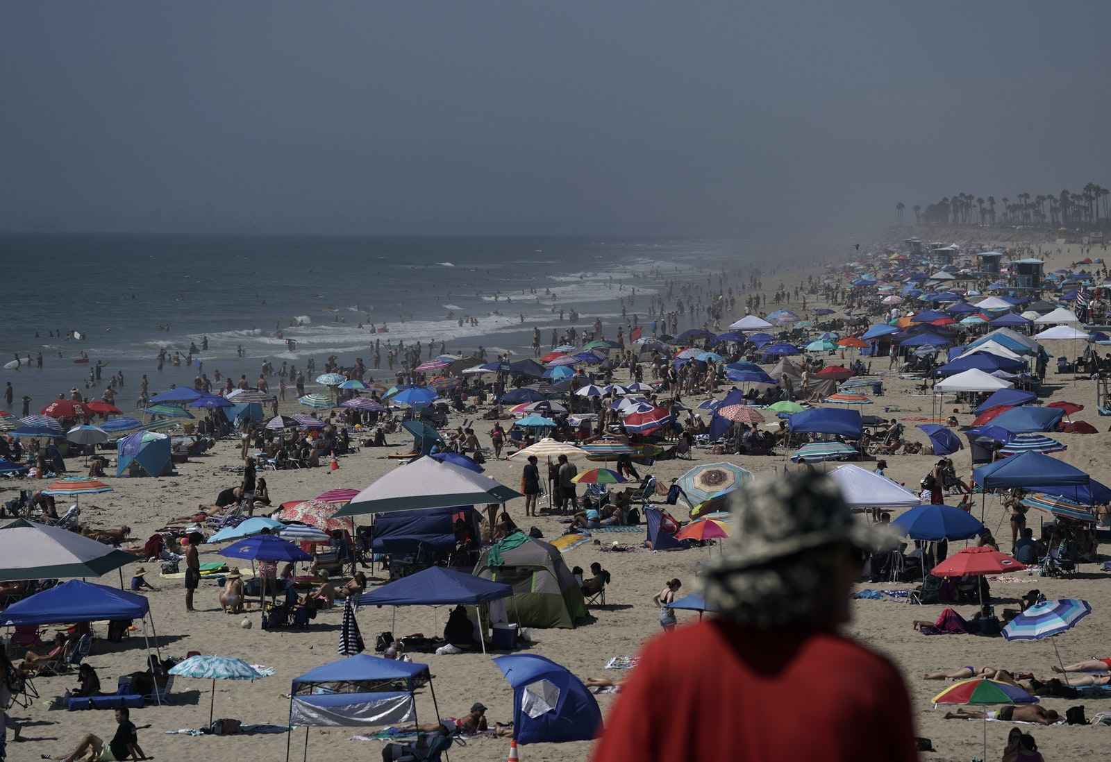 People crowd the beach in Huntington Beach, Calif.,