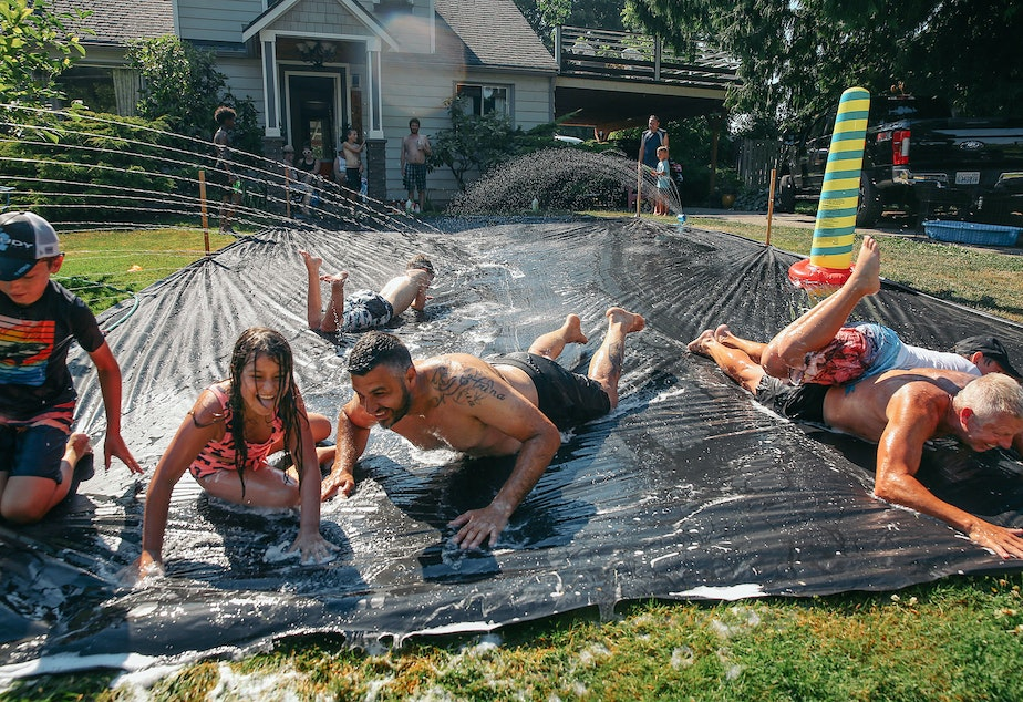 caption: Vasili Vouros, center, and John Cain Jr., right, slip n' slide with their kids in Vouros's front yard in Skyway, Monday, June 28. The National Weather Service recorded 108 degrees in SeaTac on Monday, setting an all-time record for the area. A car temperature gauge recorded 109 degrees in Skyway at 4:30 pm.