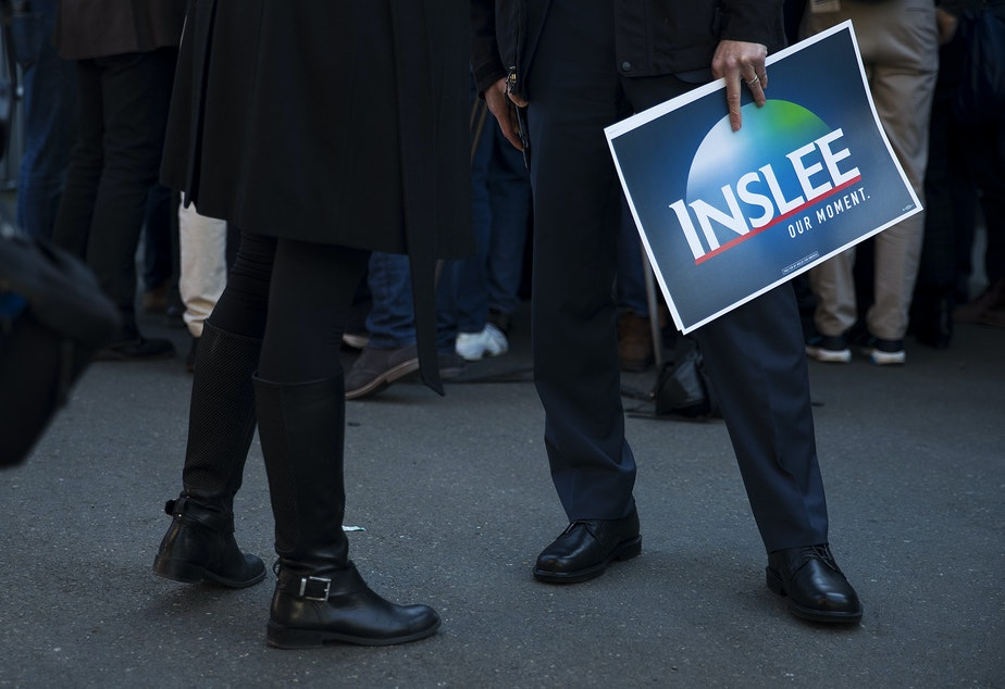 Attorney General Bob Ferguson, right, holds an Inslee Our Moment sign after Governor Jay Inslee announced his candidacy for president on Friday, March 1, 2019, at A&R Solar on Martin Luther King Jr. Way in Seattle.