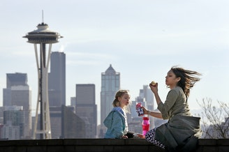 Nora Kennelly, 3, picnics with her nanny, Ty Messiah, in the sun atop a wall overlooking the Space Needle and downtown Seattle, Monday, Feb. 8, 2016.
