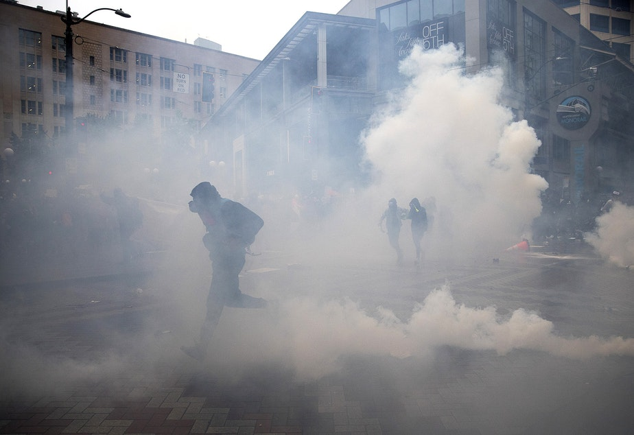 caption: Thousands gathered in protest following the murder of George Floyd on Saturday, May 30, 2020, in Seattle. Here, protesters run from tear gas and flash bang grenades deployed by Seattle police officers near Westlake Park. For over 150 consecutive days, protesters demanding racial justice and an end to police brutality continued to march in Seattle.