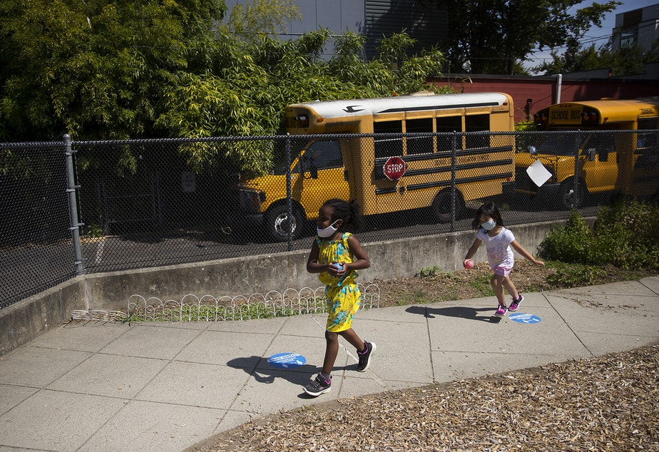 caption: Students play a game on the playground after collecting flowers on a walk with teacher Margarita Arias on Thursday, July 16, 2020, at the Denise Louie Education Center along Beacon Avenue South in Seattle.