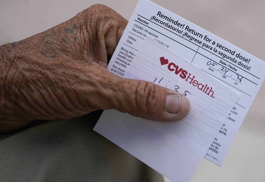 caption: A man holds his vaccination reminder card after having received his first shot at a pop-up vaccination site next to Maximo Gomez Park, also known as Domino Park, on May 3, 2021, in the Little Havana neighborhood of Miami.